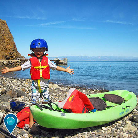 photo of kid and a kayak