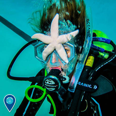 photo of a diver with a starfish on her face