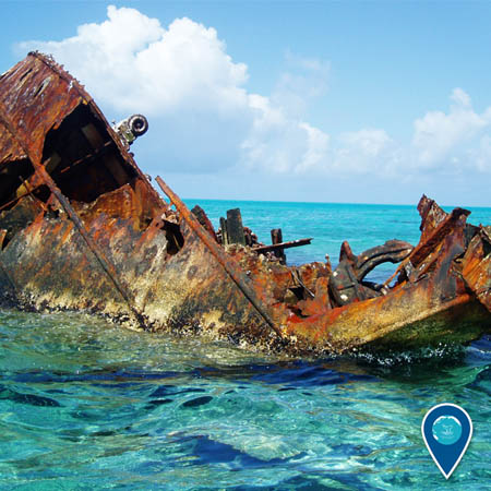 photo of shipwreck in shallow water