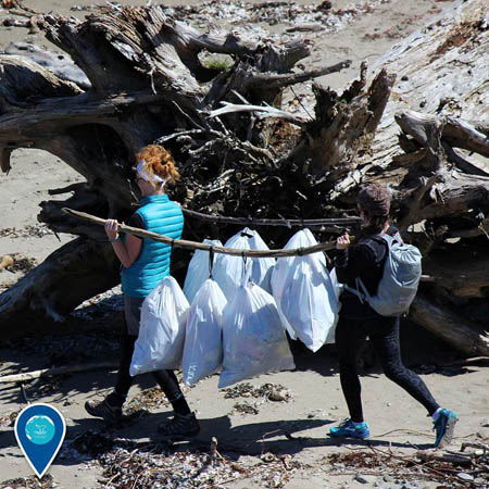 photo of girls cleaning up a beach
