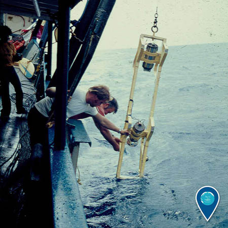 photo of a scientists lowering equipment into the ocean