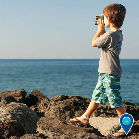 photo of a boy with binoculars looking out into the ocean