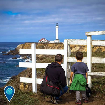 photo of a man and his son looking at a lighthouse