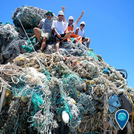 photo of 4 people standing on a pile of nets and ropes that are marine debris