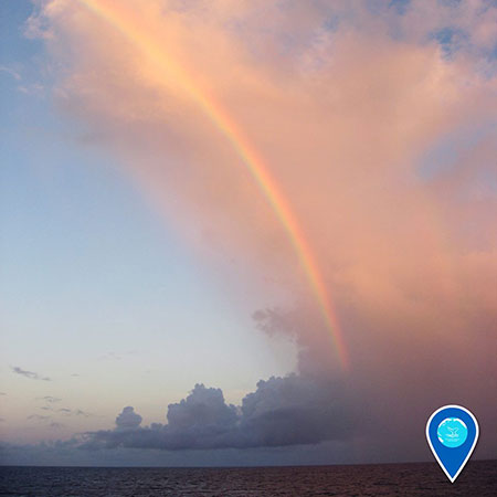 photo of a rainbow over the ocean