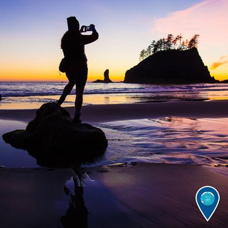 person standing on a rock on the beach taking a photo of the sunset with cannonball island in the back ground