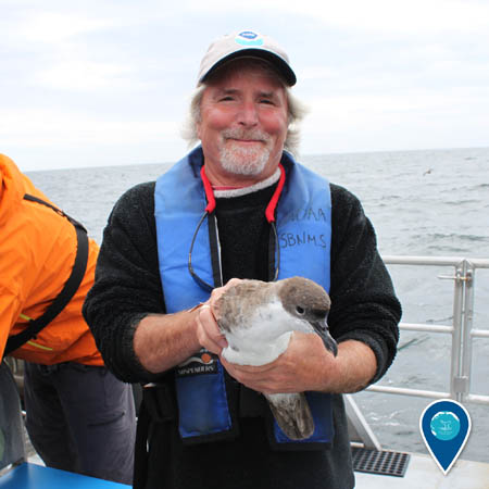 researcher david wiley holding a seabird aboard a ship