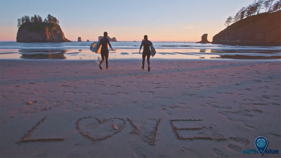 photo of a beach with people looking at the sunset with the words love written in sand
