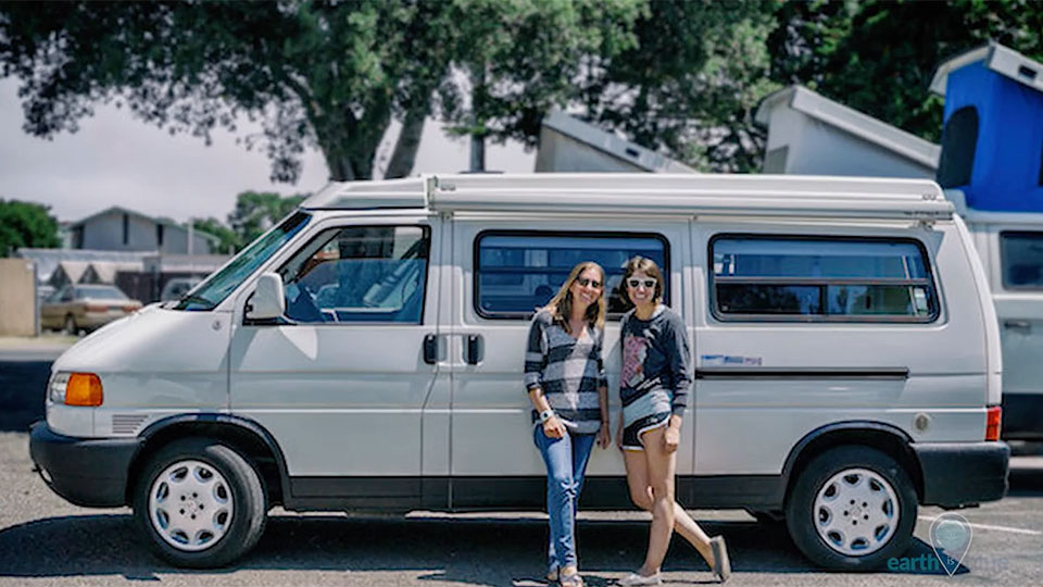 2 women standing in front of a white van
