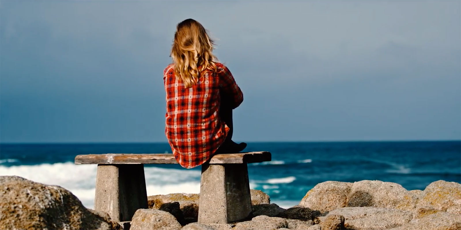 woman sitting on a bench looking at the ocean