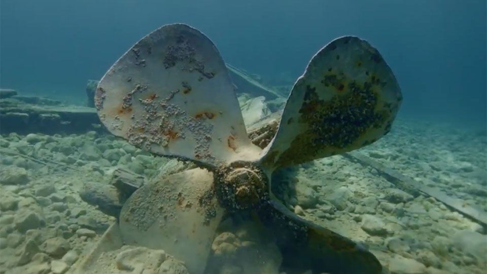photo of a propeller from a shipwreck under water