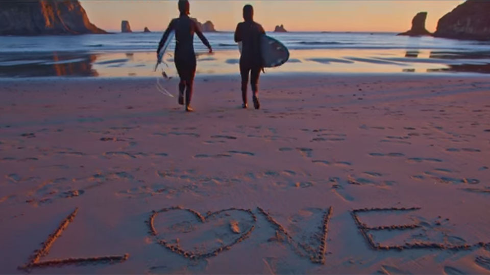 photo of 2 surfers and the word love written on the sand