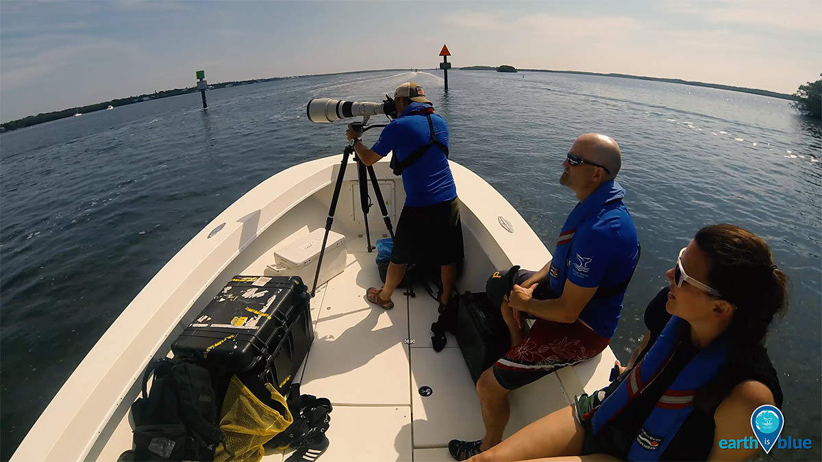 three sanctuaries employees on the deck of a boat taking photos