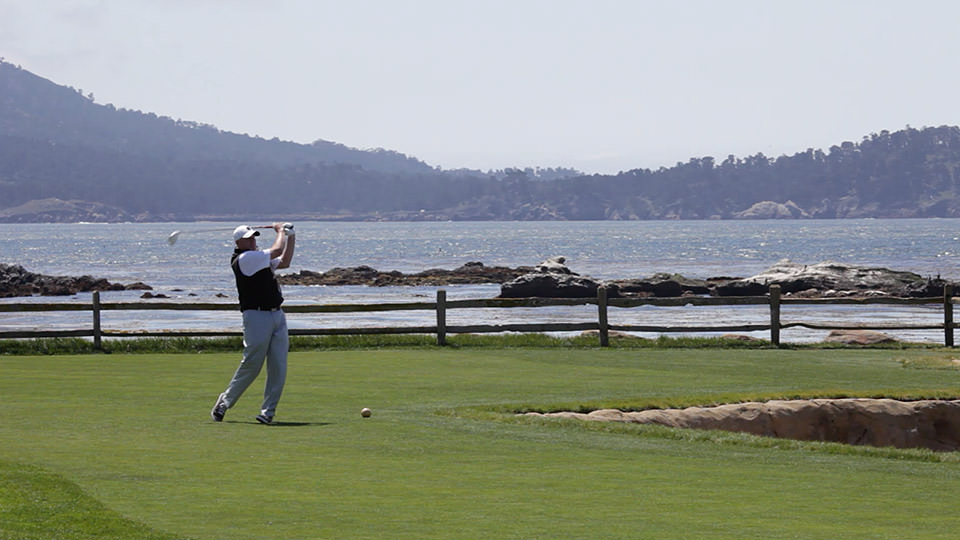 A golfer finishes his swing with water in the backdrop