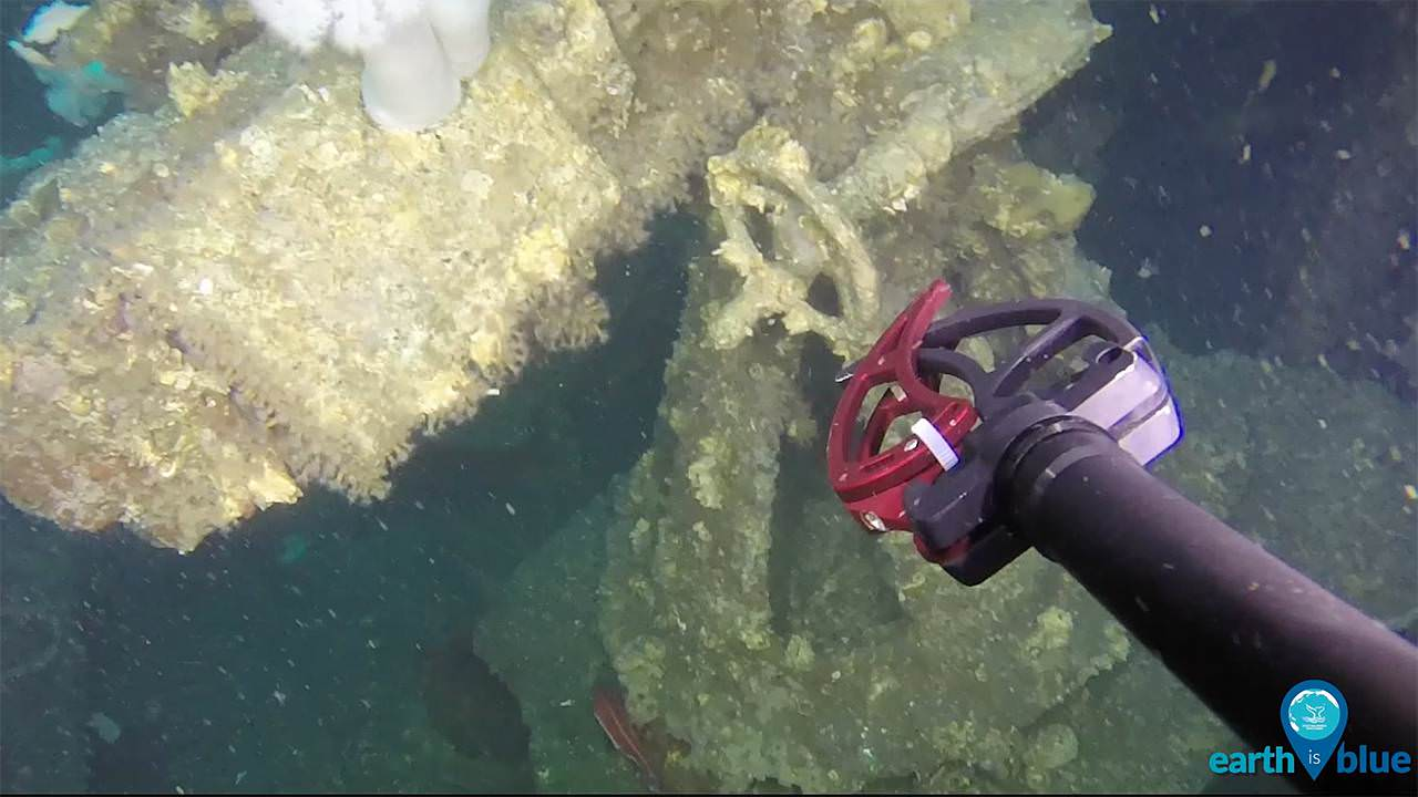The arm of an rov reaches toward a shipwreck