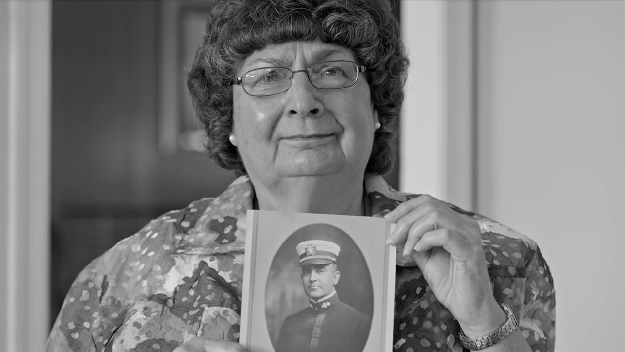 photo of a woman holding up a picture of a family member who perished on the USS Conestoga