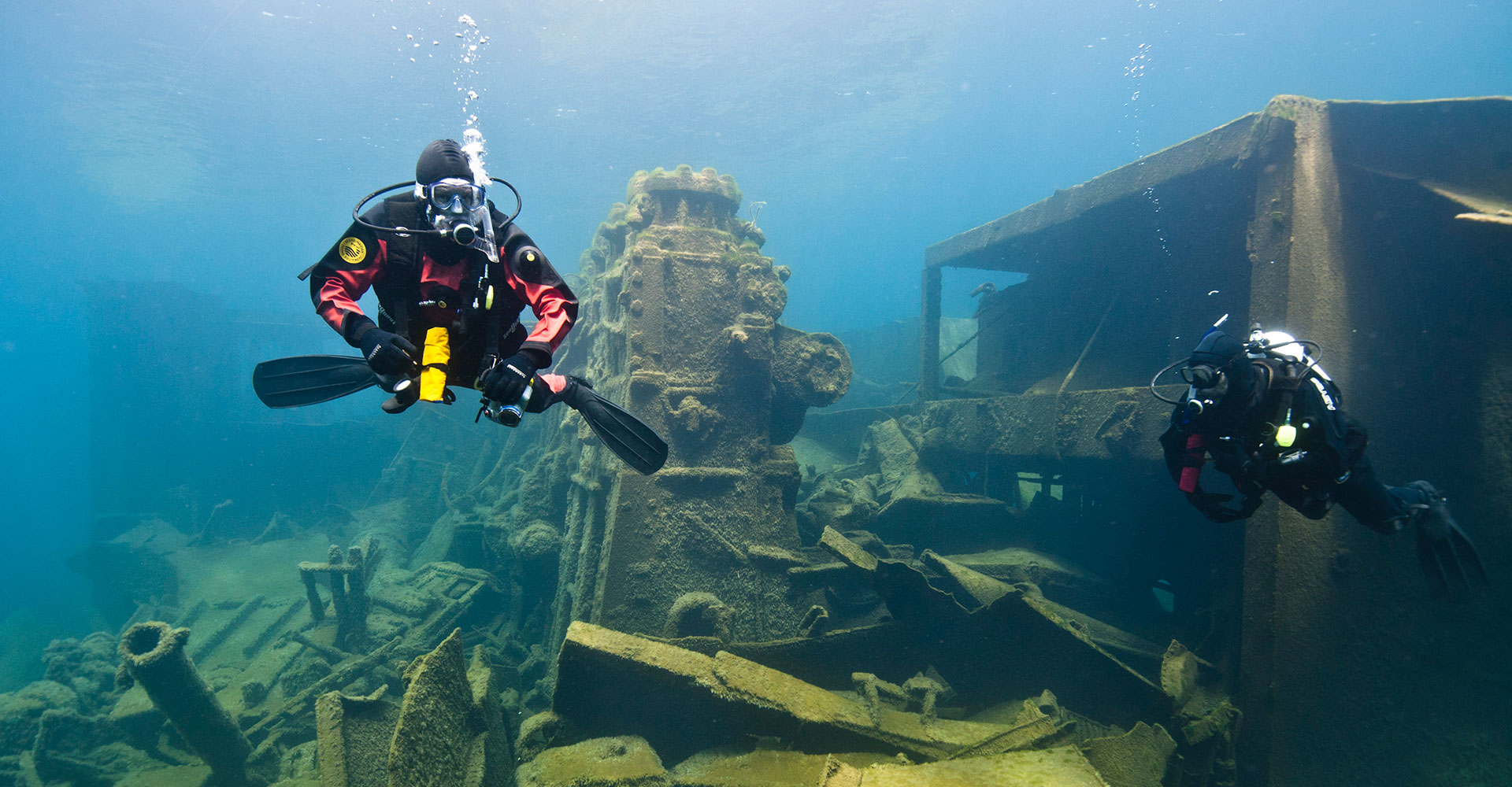 2 divers on and a shipwreck underwater