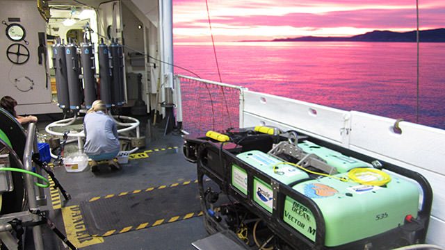 sunset on the deck of the bell m. shimada, two scientist work on a water collection device next to the rov