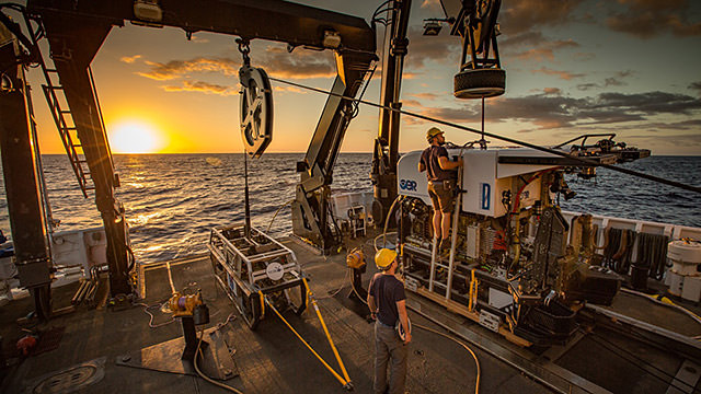 two memeber of the okeanos crew prepare an rov on deck