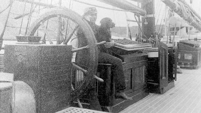 Captain Michael A. Healy with a dog sitting at the wheel of the steam cutter bear