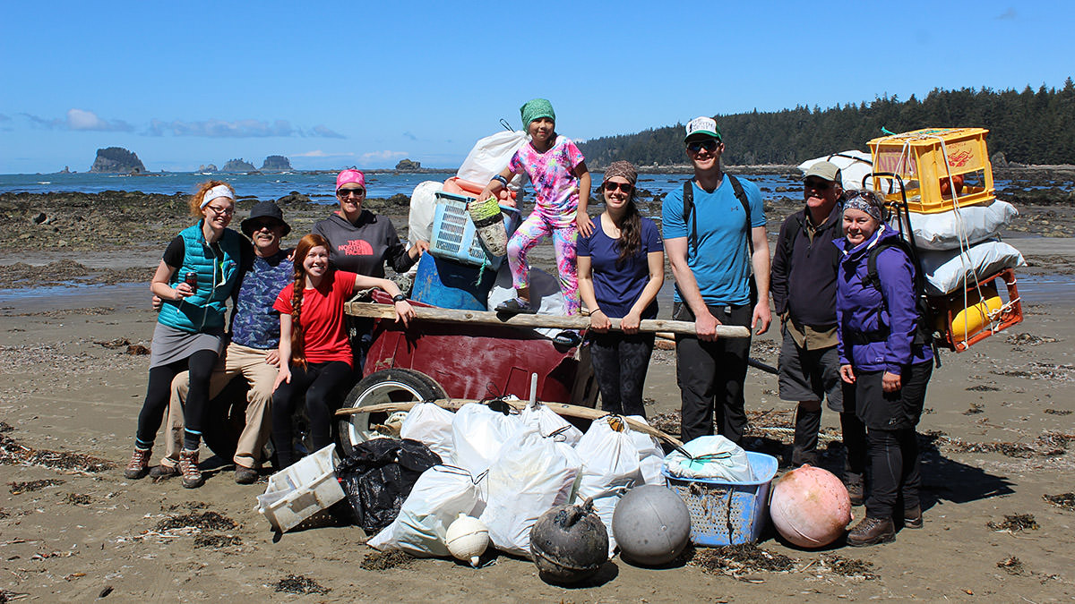 group of volunteer posing with the marine debris they collected along the beach