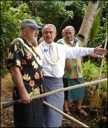 Daniel J. Basta, program director and Togiola T.A. Tulafono, Governor of American Samoa, take a moment to admire the new trail. They are holding traditional salutus used to sweep the trail's entrance.