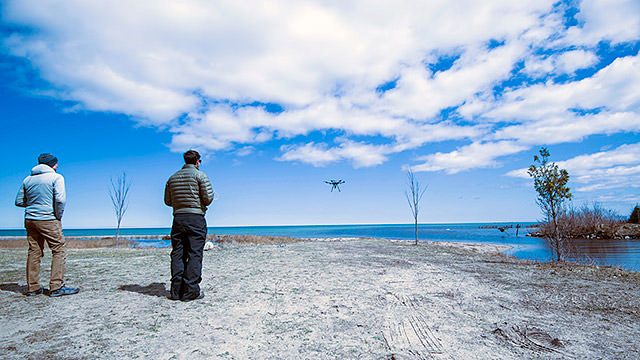 uas pilot controlling a uas in the background