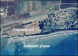 Figure 13. A sediment plume in this aerial photograph off the coast of Kaua'i. The sediment was transported by runoff from fields where soil is exposed. (Photo: Georeferenced NOAA/NOS aerial photography by Pacific Disaster Center in 2000)