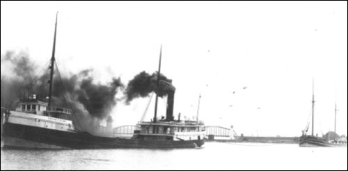 Figure 11. The steam barge Oscar T. Flint with a schooner barge in tow. Carrying bulk cargo in its own hold, while towing additional barges known as consorts, allowed the steam barge to maximize the amount of cargo conveyed in a single trip. Barges were often aging schooners, as seen here. In 1909, the Flint caught fire and sank in 30 feet of water in Thunder Bay (Historical Collections of the Great Lakes, Bowling Green State University).