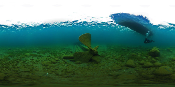 a diver photographs the propeller of tugboat City of Alpena, a boat can been seen above the diver