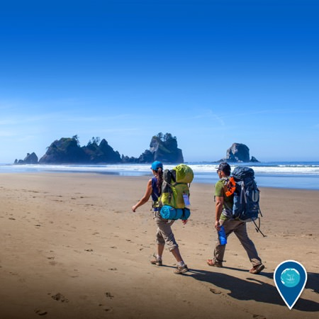 backpackers walk along Shi Shi Beach in Olympic National Park