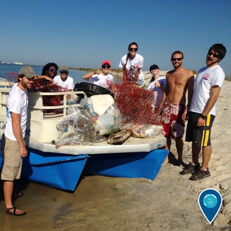 group of people posing with marine debris they have collected