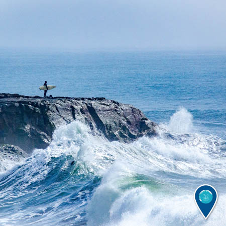 surfer standing on a rock cliff looking out at the ocean while wave crash round him