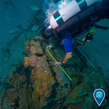 diver takes measurements on a small engine at an unknown shipwreck
