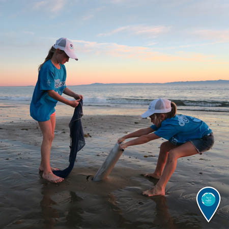 two kids cleaning up marine debris from the beach