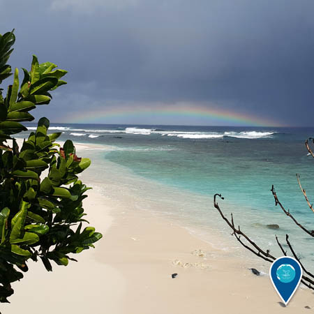 shoreline of american samoa, a rainbow can be seen in the background