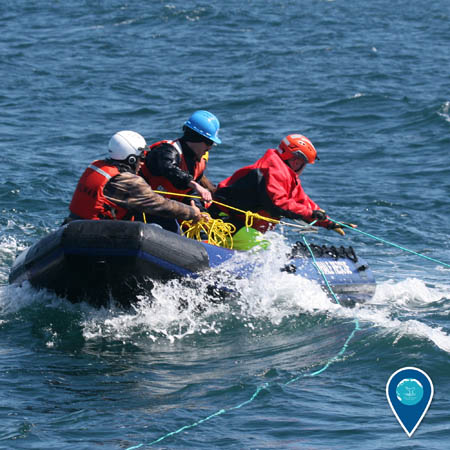 Three people wearing helmets pull on rope while aboard a small inflatable boat