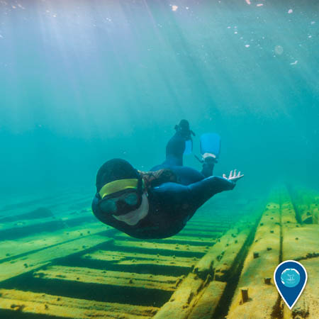 A female snorkeler swims over the flattened remains of a wooden shipwreck. The water is blue while the shipwreck appears greenish-yellow.