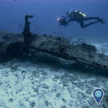 A diver carrying a camera swims above a sunken aircraft wing.