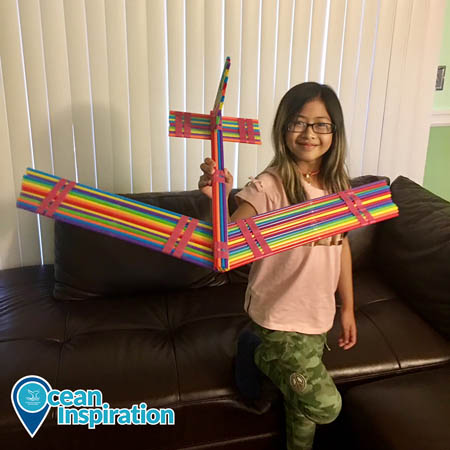 A girl holding an airplane made out of multicolored straws.