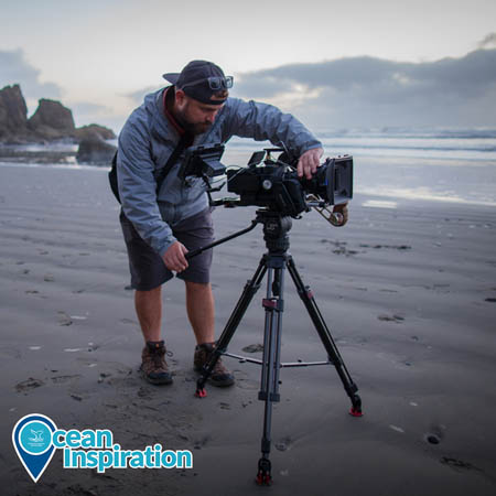Nick stands on a beach, leaning over a video camera set up on a tripod. This image was taken on Ruby Beach in NOAA Olympic Coast National Marine Sanctuary, and the ocean and sea stacks are visible in the background.