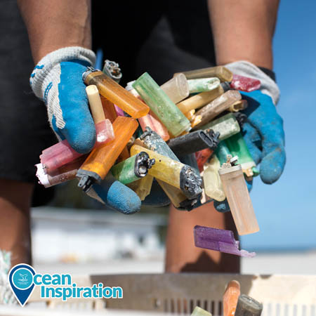 A person in Papahānaumokuākea Marine National Monument adds a large handful of brightly colored plastic lighters to a bin. Only the person's arms are clearly visible; they are wearing work gloves. This is a photo from the annual cleanup of remote islands within the monument.