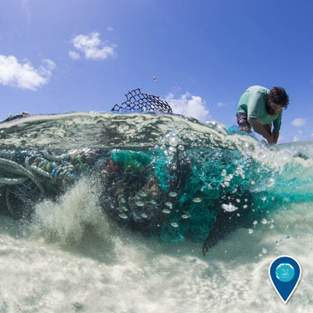 A person bends over a large conglomeration of fishing nets and other debris that is submerged in shallow ocean water.