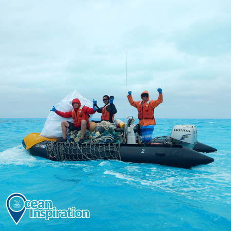 Three people on an inflatable boat holding their hands up in celebration; the boat is holding piles of nets and other debris.