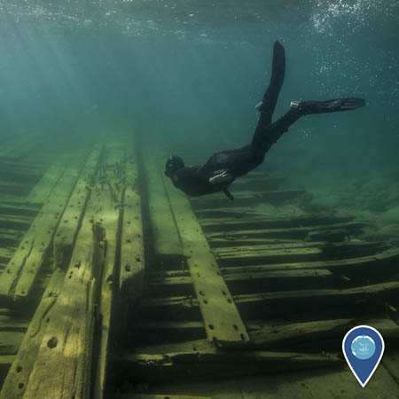 A snorkeler swims beneath the water, just above the wooden remains of a shipwreck.