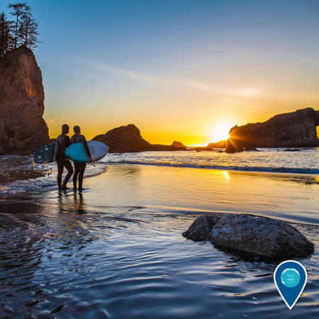 Two surfers stand on the beach at sunset in Olympic Coast National Marine Sanctuary.