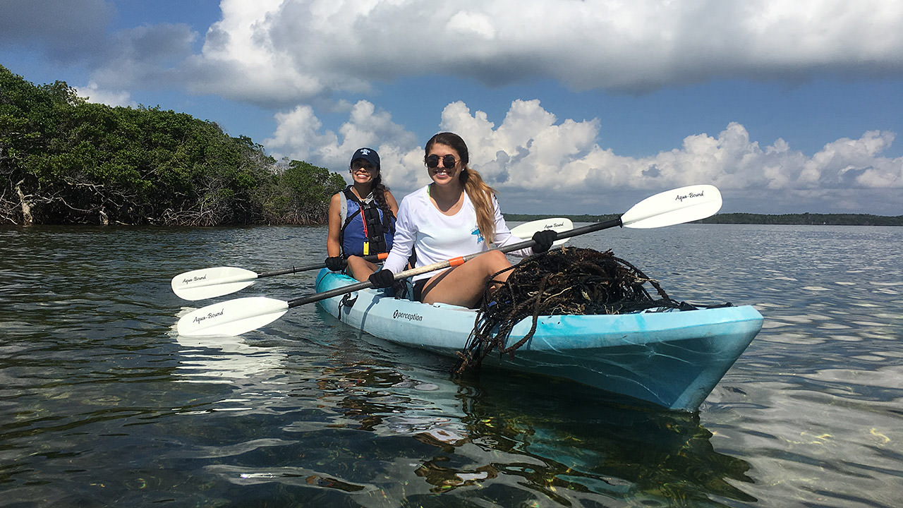 a pair of kayakers with marine debris they collected on their kayak