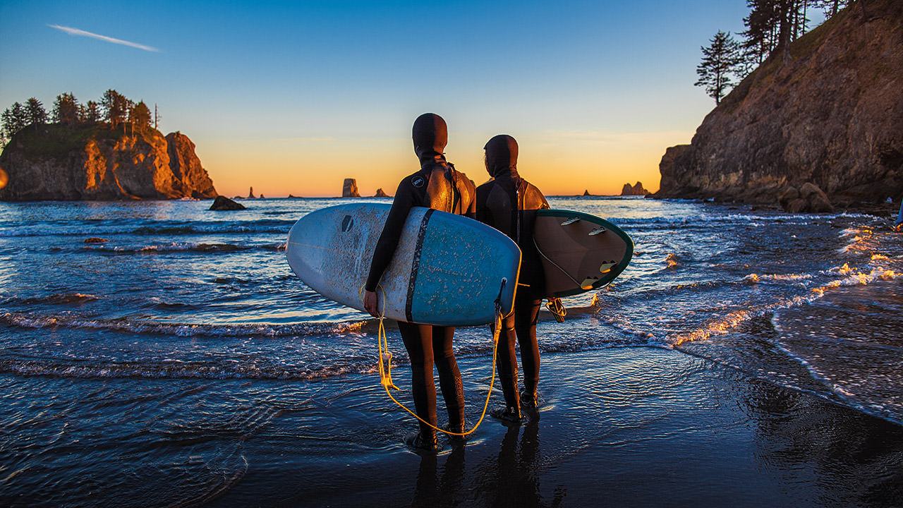 a surfer and bodyboarder standing on the beach looking at the water