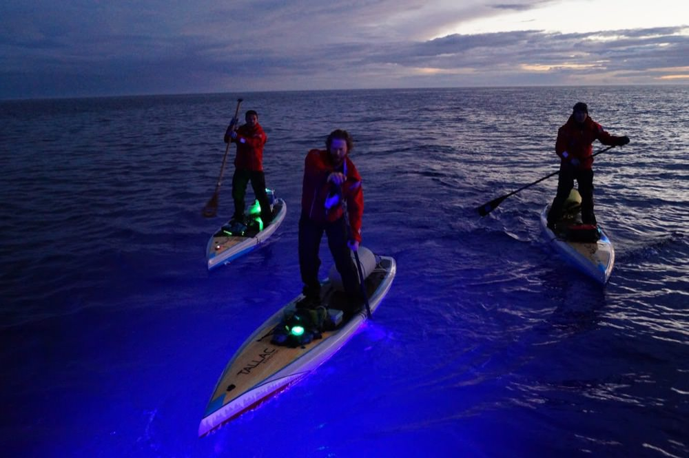 Joe Lorenz, Jeff Guy, and Kwin Morris paddleboarding at night with colored lights