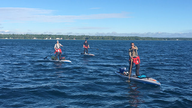 Joe Lorenz, Jeff Guy, and Kwin Morris paddleboarding
